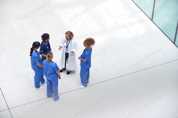 Overhead View Of Female Medical Staff Having Informal Meeting In Lobby Of Modern Hospital Building