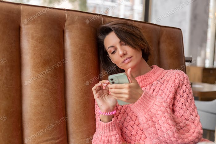 Woman in a restaurant in a warm sweater is looking at something on the phone