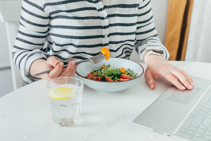 Young woman eating salad at desk. Delicious balanced food concept. Home office