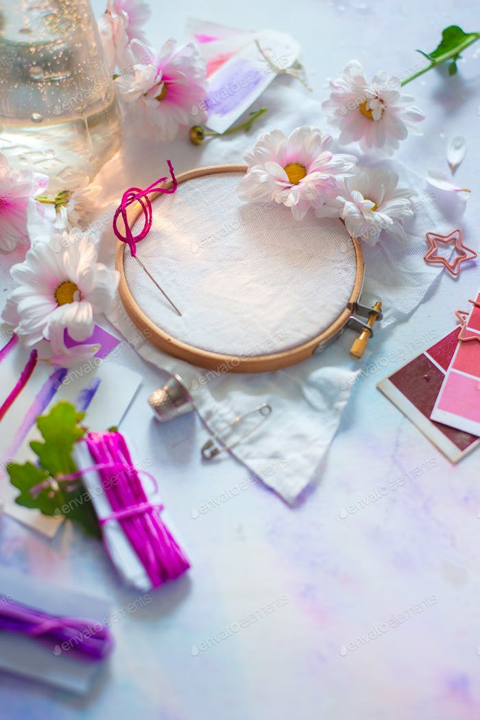 Pink, white and purple pastel tones embroidery frame close-up with flowers.