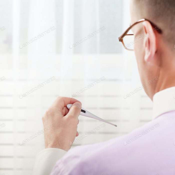 Man read measurement result from digital thermometer