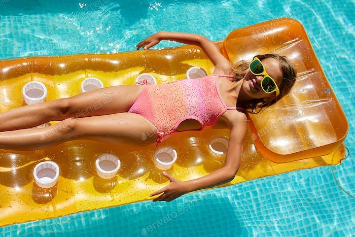Kleines Mädchen in Sonnenbrille entspannt im Schwimmbad, schwimmt auf aufblasbaren gelben Matratzen