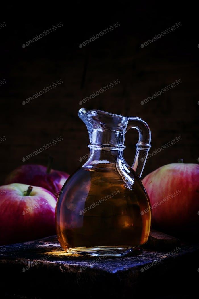 Apfelessig in einem Glaskanne, frische Äpfel