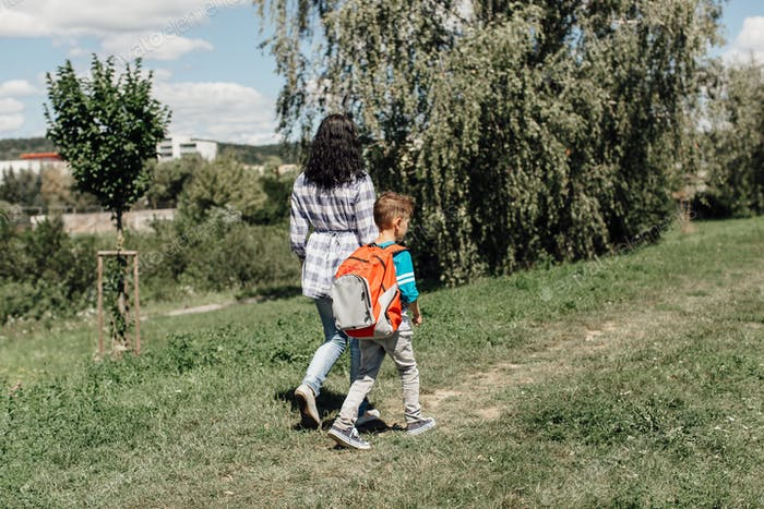 Rear view of a schoolboy and his mother walking to school together