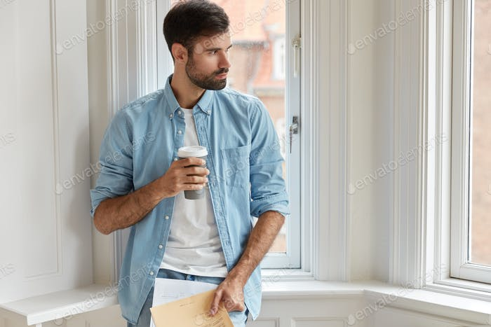 Photo of bearded administrative mamager holds papers, disposable cup of coffee, looks aside thoughtf