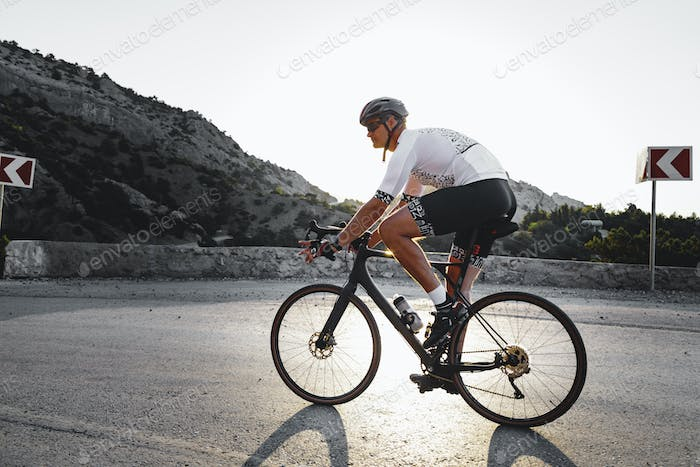Professional road bicycle racer in action on mountain road