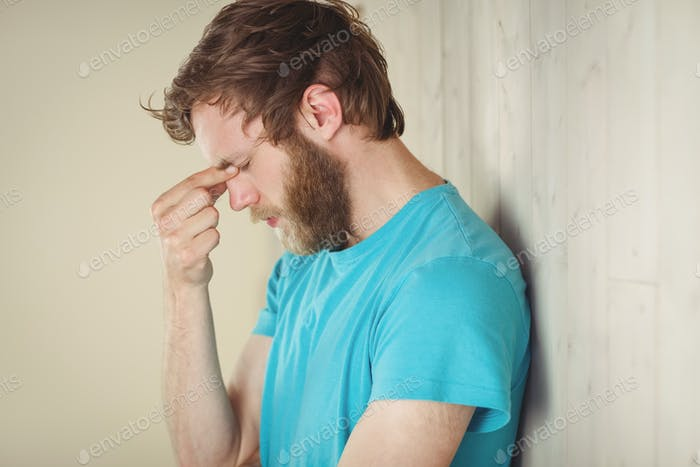 Troubled hipster leaning against wall in side view
