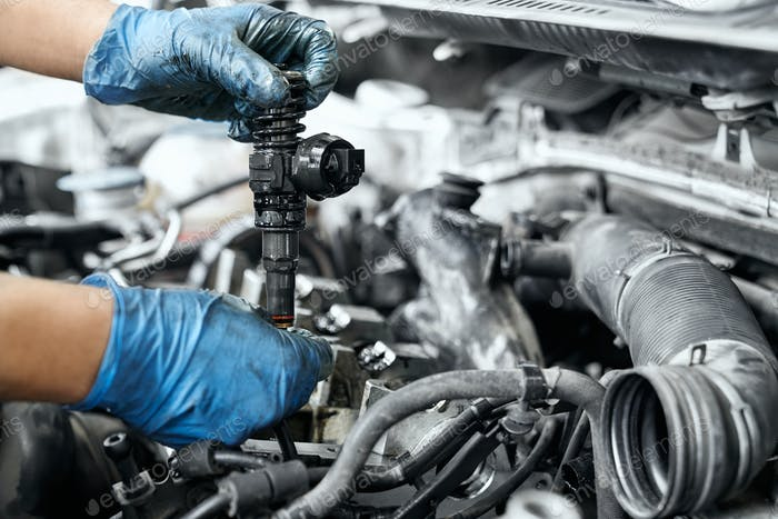 Male specialist replacing ignition coil and old nozzles