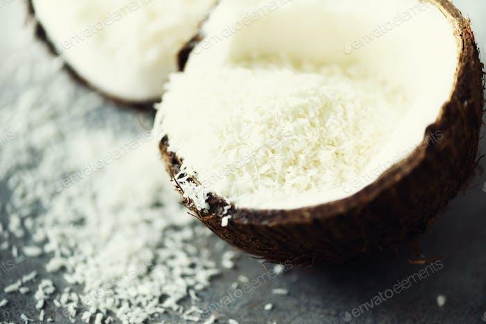 Coconut fuit halves with coconut shavings on grey concrete background. Copyspace