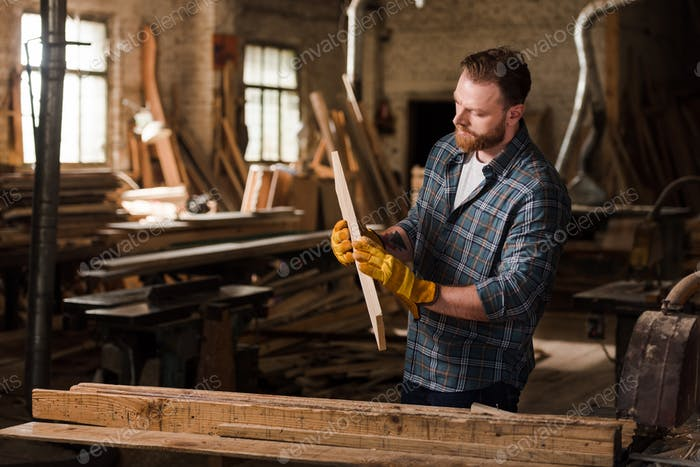 bearded carpenter in protective gloves working with wood at sawmill