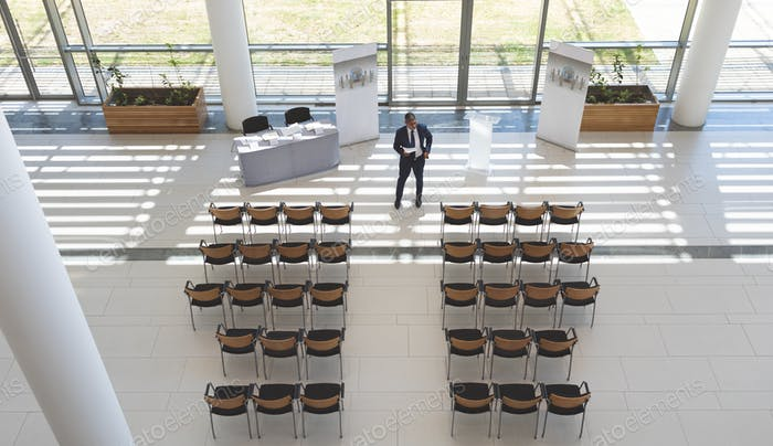 High angle view of businessman practising speech in empty conference room in modern office building