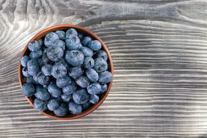 Blueberries in clay bowl on wooden table
