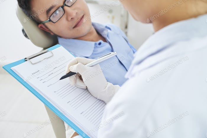 Dentist Writing Something In Medical Record