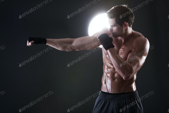 Young muscular guy with a naked torso boxing