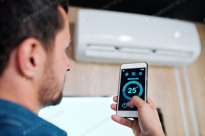 Young man using smart application to adjust temperature of air conditioner