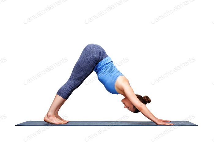 Beautiful sporty fit yogi girl practices yoga asana adhomukha sv