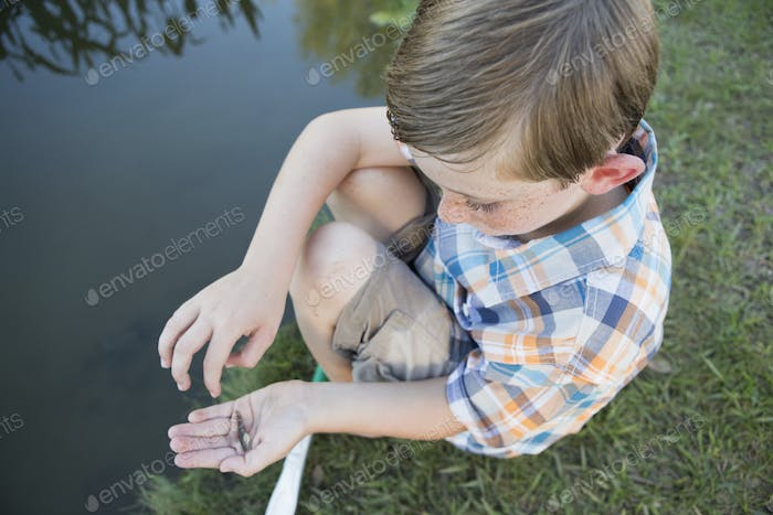 A young boy outdoors sitting on a riverbank with a small fish in the palm of his hand.