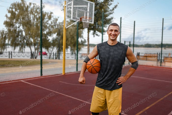 Muscular basketball player on outdoor court