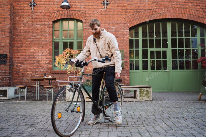 Young casual bearded man standing with old classic bicycle on city street