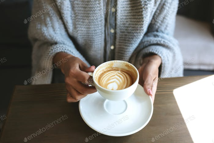 Young woman hands holding white cup of coffee and saucer in restaurant