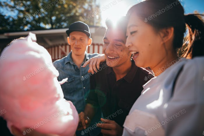 Three friends eating candy floss