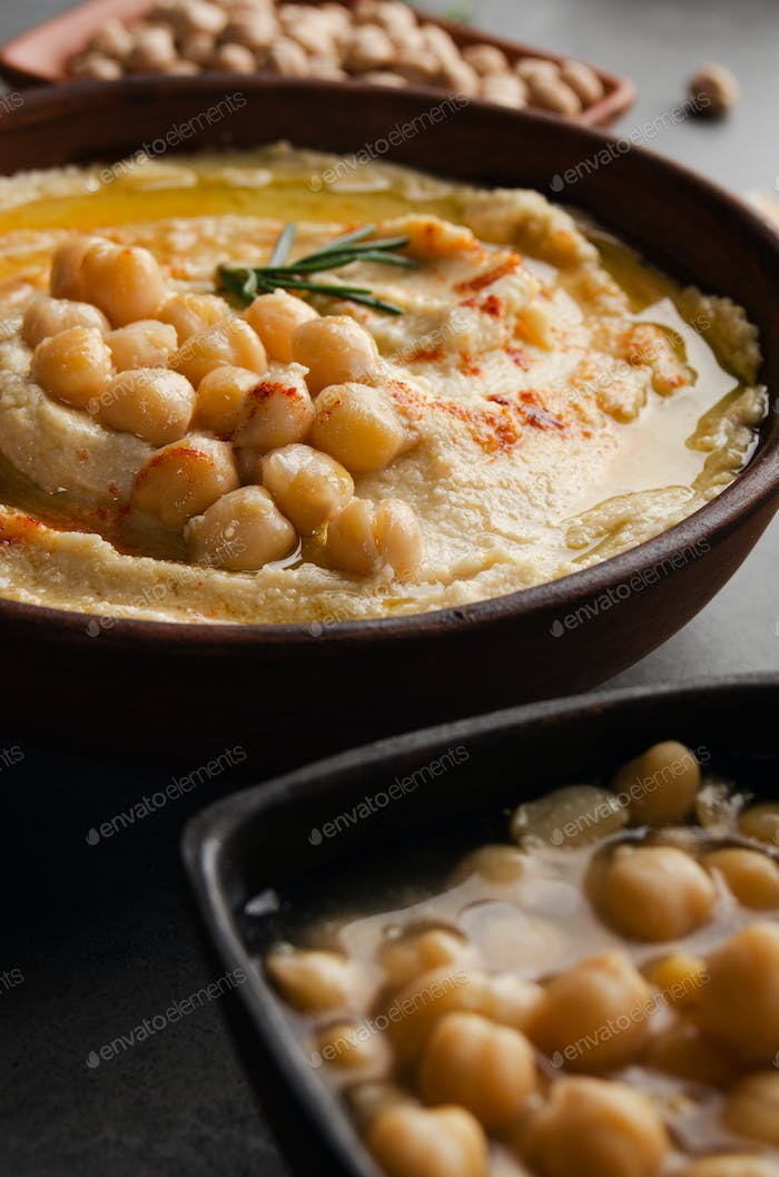 Closeup view at Hummus topped with beans olive oil and green rosemary leaves on kitchen table