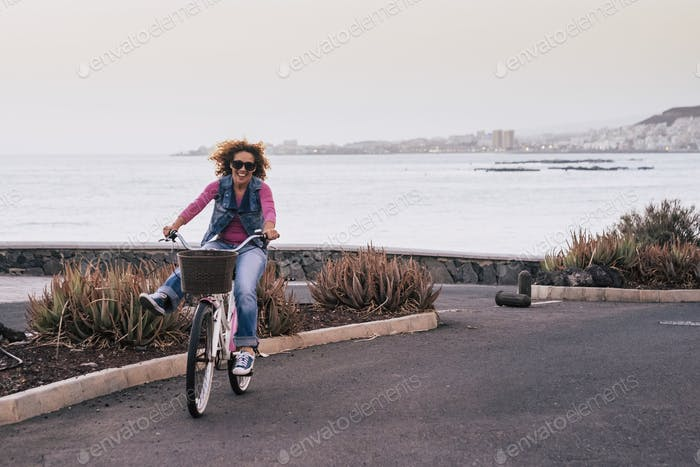 nice beautiful young caucasian woman with curl hair in the wind ride a bike and have fun enjoying