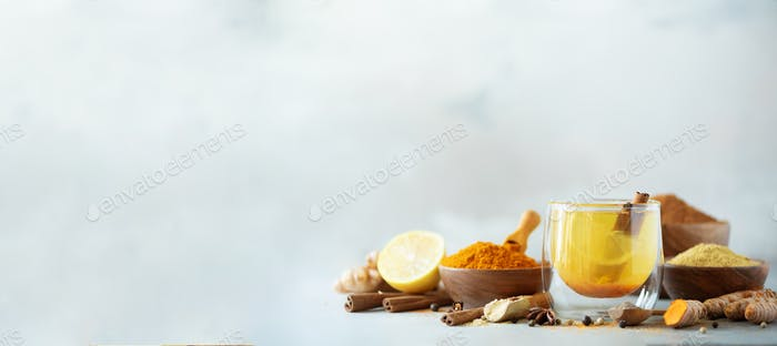 Ingredients for turmeric hot tea on grey background. Healthy ayurvedic drink with lemon, ginger