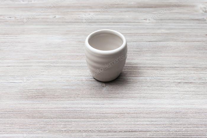 weiße Tasse für Sake auf graubraunem Holztisch