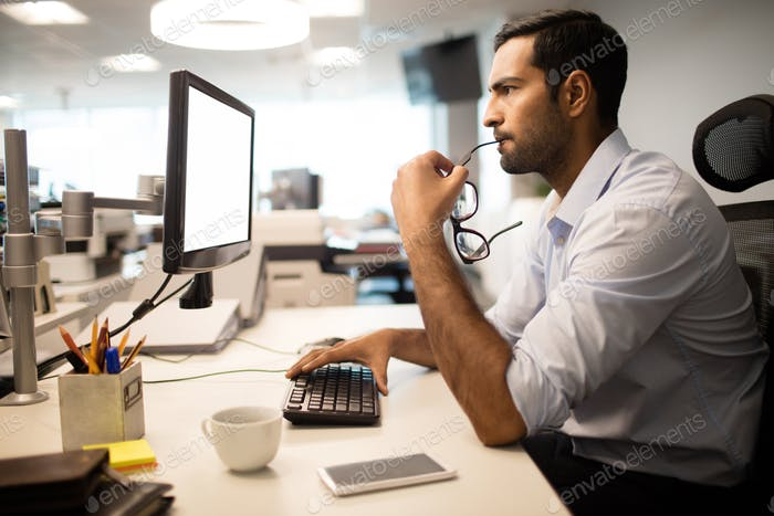 Thoughtful businessman using computer in office