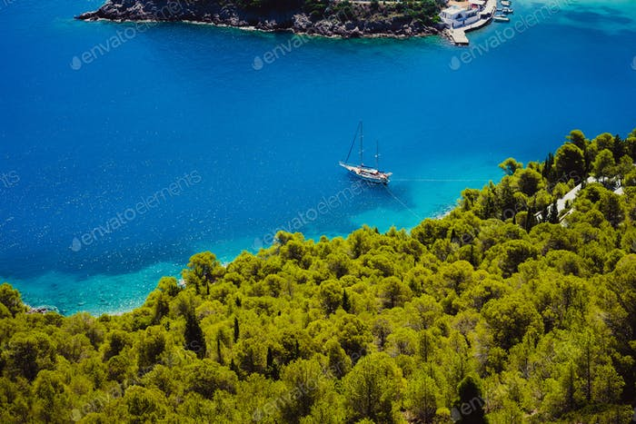 Top view of white lonely yacht in beautiful turquoise colored bay lagoon water surrounded by pine