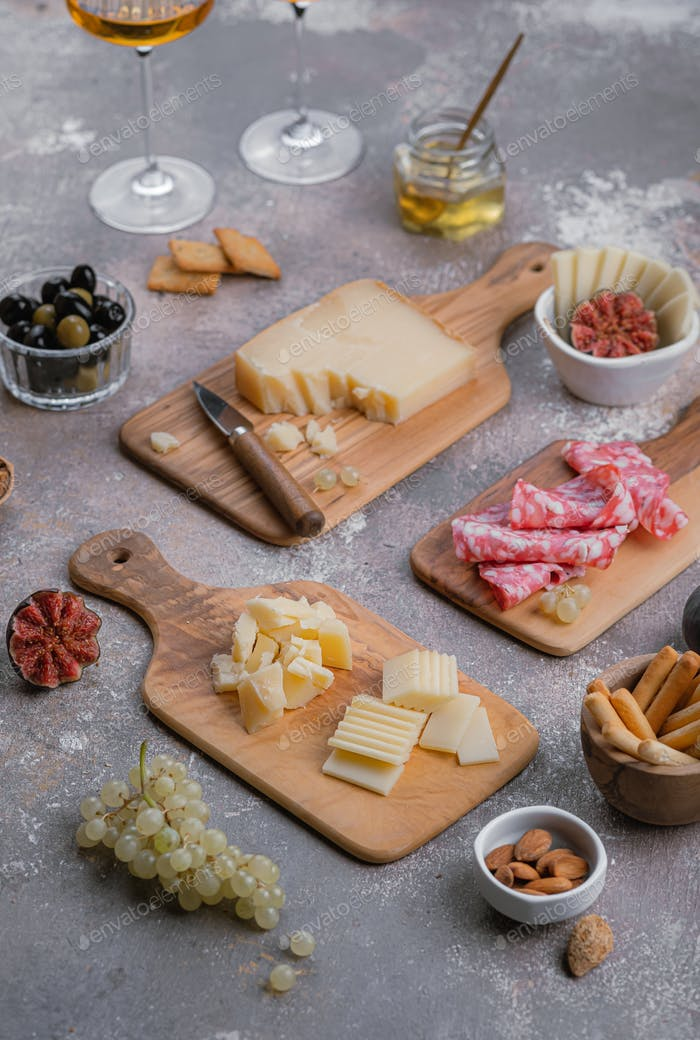 Wooden boards full of delisious appetizers cheese, salumi, grapes, honey and nuts