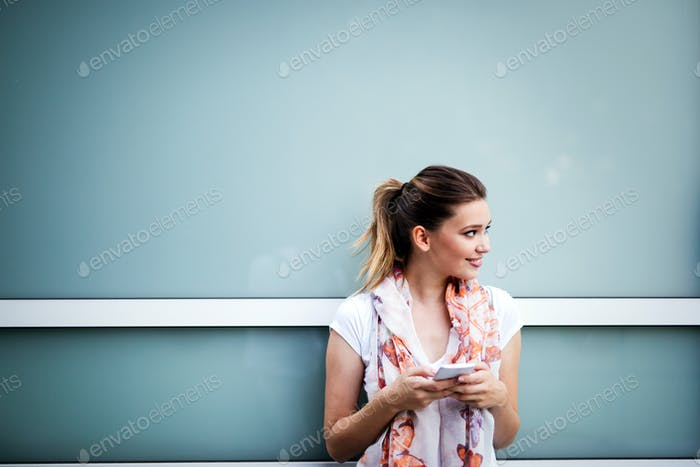 Beautiful woman using a smartphone on street. Social network, technology, busy life concept