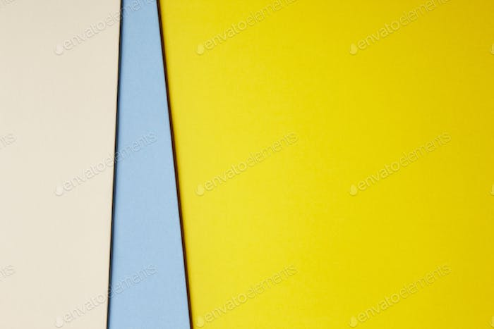 Colored cardboards background in beige blue yellow tone. Copy space. Horizontal