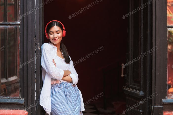 Pretty smiling girl in white shirt happily closing eyes leaning