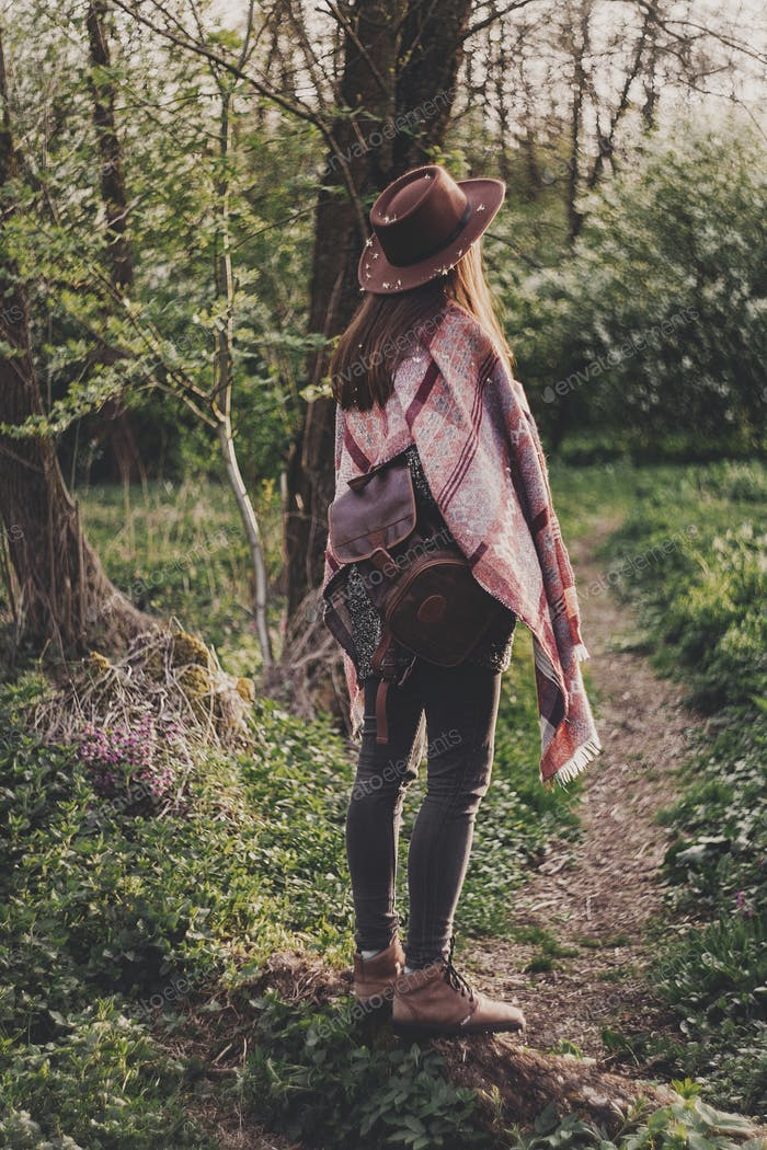 stylish hipster girl in hat with backpack walking in woods in evening sunshine
