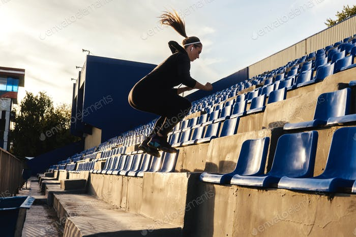 Fitness woman jumps on the stairs outdoors.