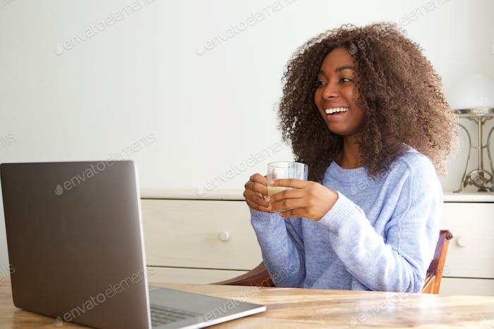 glückliche junge afrikanische Frau sitzt am Tisch und Blick auf Laptop