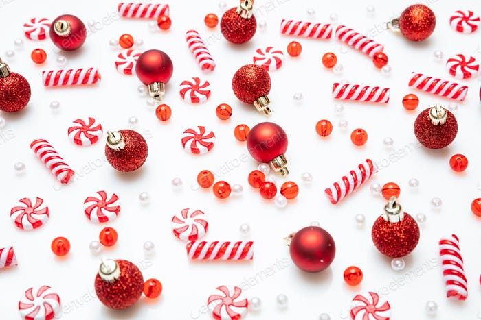 Xmas baubles and candies flat lay against white background