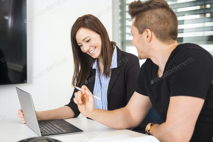 Businesswoman Using Laptop By Colleague At Desk