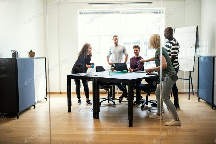 Young designers playing table tennis inside of an office boardroom