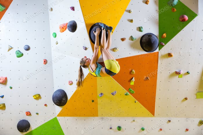 Young woman climbing bouldering route