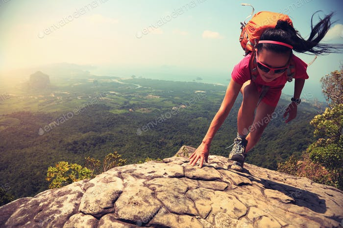 Successful woman climbing up on mountain top cliff edge