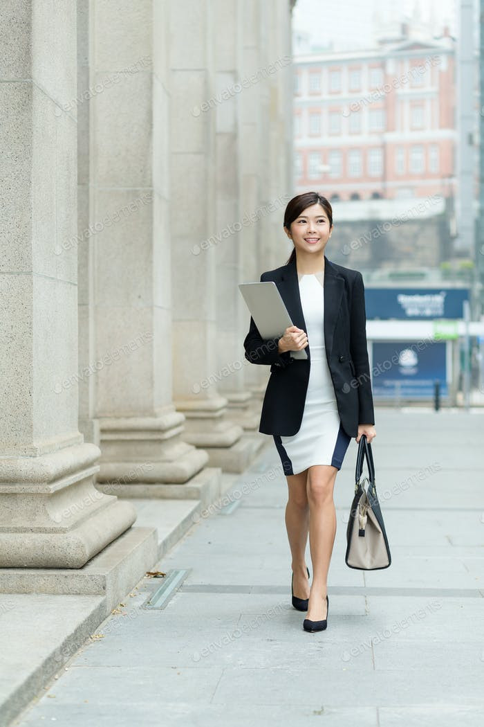 Businesswoman holding a hand bag and laptop computer