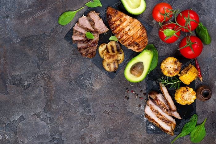 Fresh three types of grilled steak on slate plate with herbs, tomato, avocado and grilled potatoes