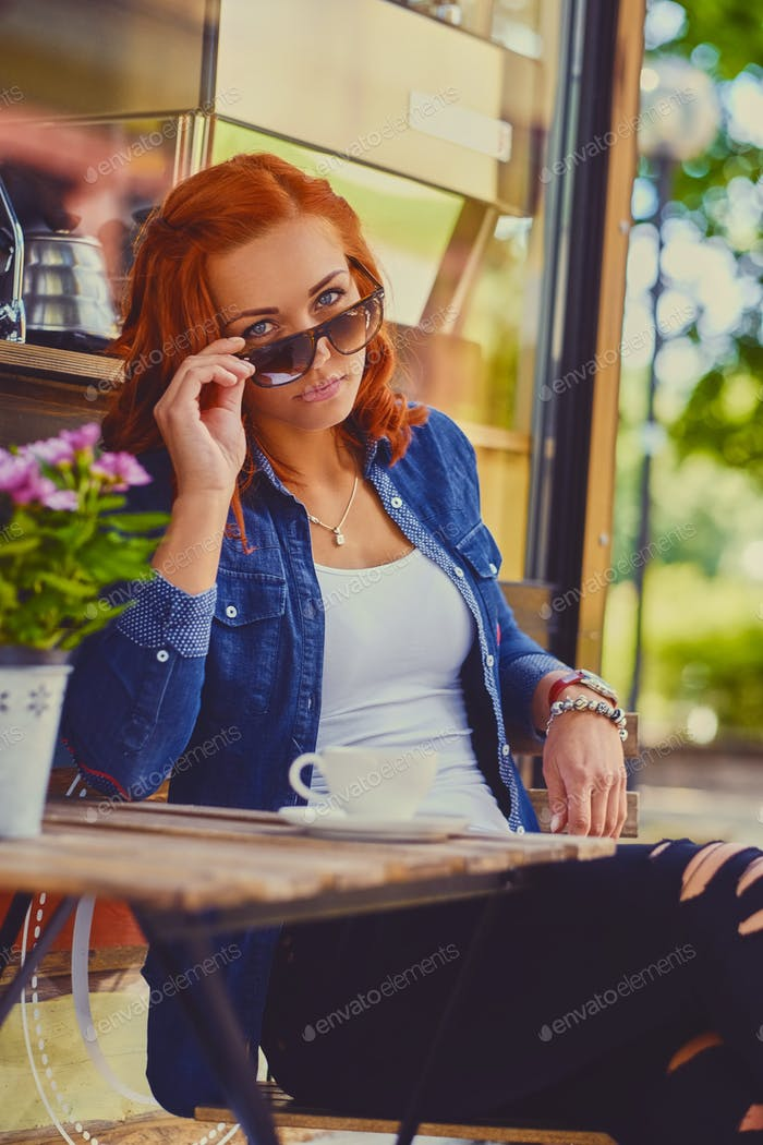 Mujer pelirroja bebe café en un café.