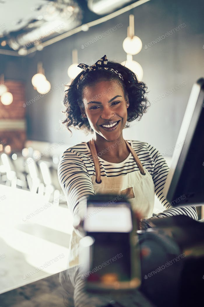 Smiling restaurant waitress holding an electronic card payment machine