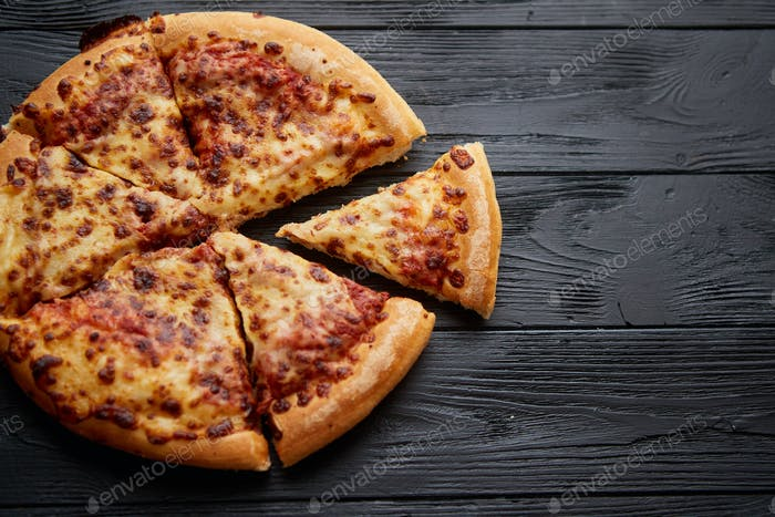 Fluffy pepperoni pizza in american style placed on rusty old black wooden table