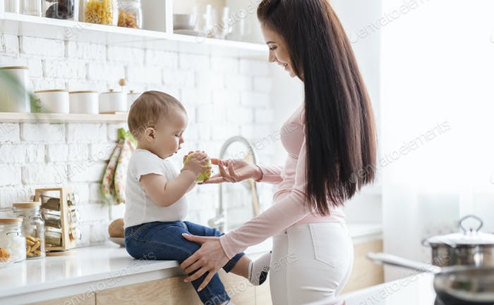 Caring mother offering fresh green apple to toddler at kitchen