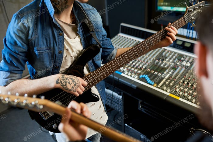 Guitarists playing music for recording
